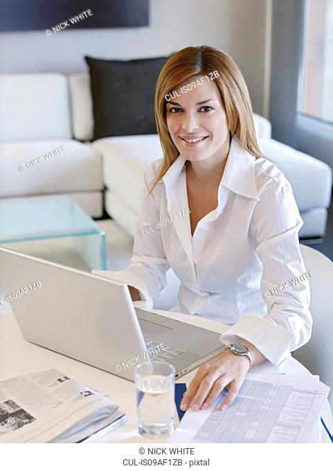 Young business woman working on computer in hotel room