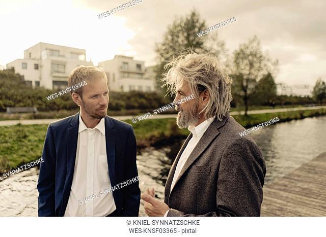 Two businessmen talking at a lake
