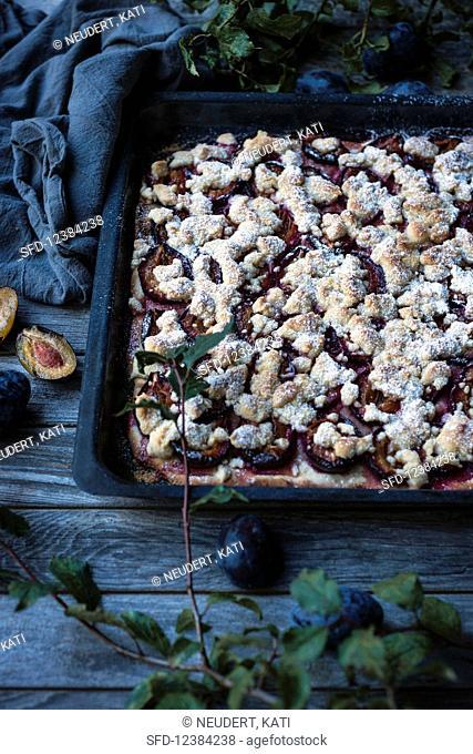 Vegan plum crumble cake in a cake tin
