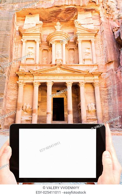 travel concept - tourist photograph symbol of ancient town Petra - Treasury Monument, Jordan on tablet pc with cut out screen with blank place for advertising...