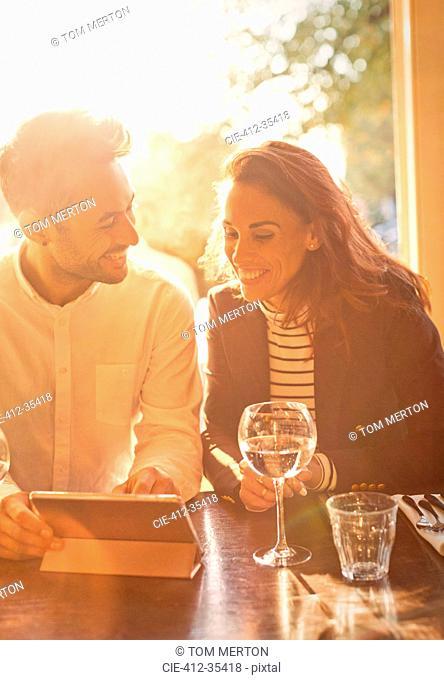 Young couple drinking white wine and using digital tablet in cafe