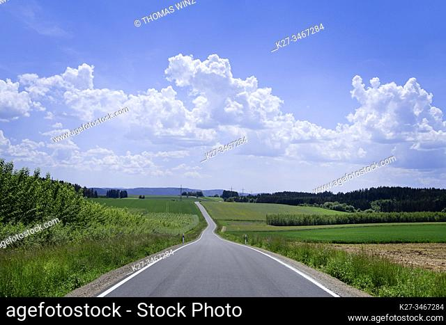 Curving country road through agricultural fields and cloudscape, Baden Württemberg, Germany