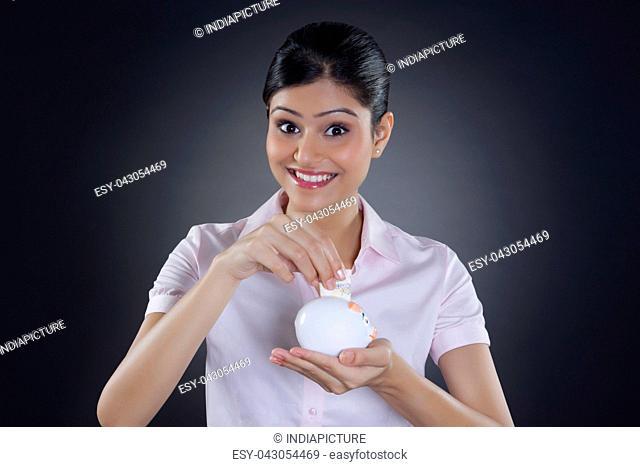 Portrait of businesswoman putting money in piggy bank