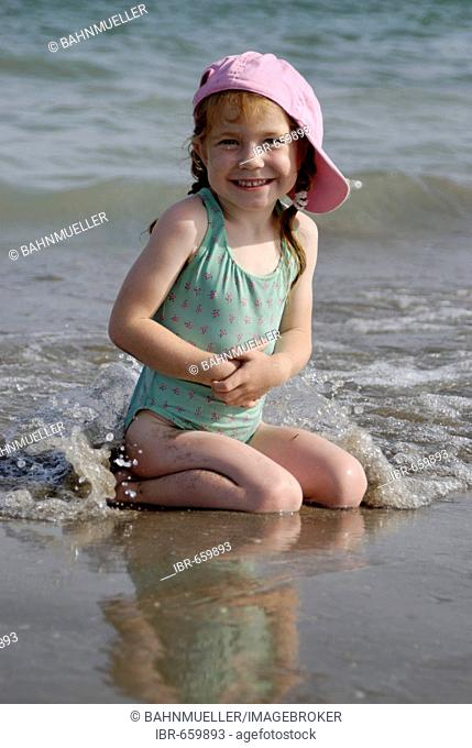 Little girl lies at a sandy beach at the sea