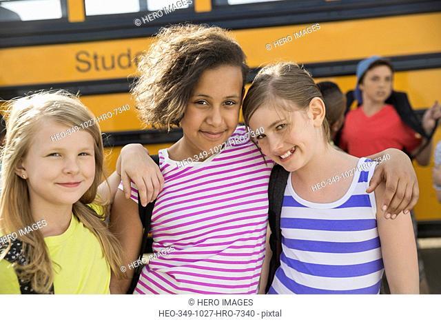 Portrait of little schoolgirls standing against bus during field trip
