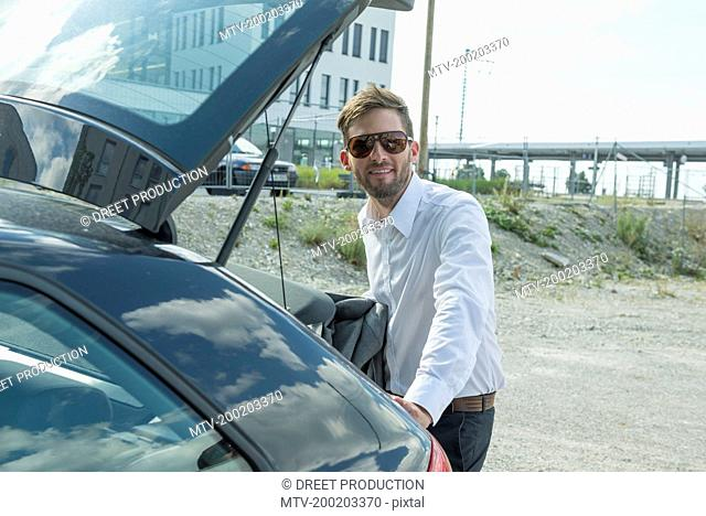 businessman with sunglasses at his car