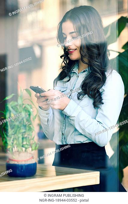 Cafe city lifestyle. Young woman sitting indoor in trendy urban cafe writing with her mobile phone. Cool young modern caucasian female model in her 20s