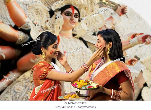 Bengali women putting colour on each others faces