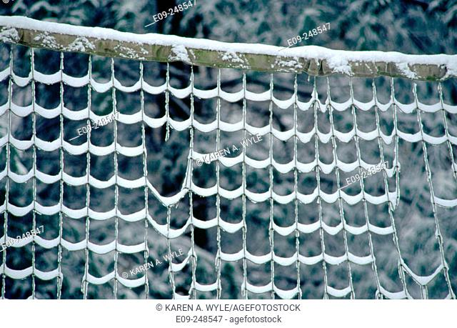 snow on volleyball net with gaps, Indiana, USA