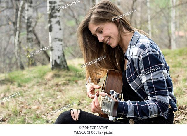Smiling woman playing guitar in forest