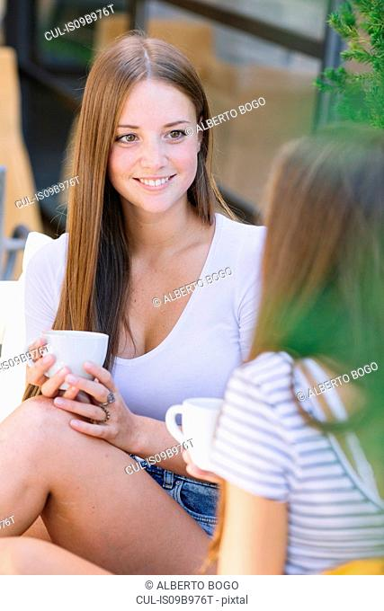 Two young female friends having coffee and chatting at sidewalk cafe