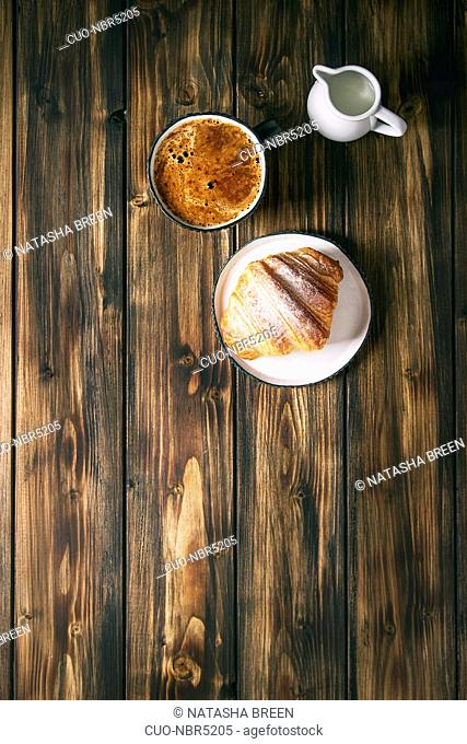 Homemade croissant with sugar powder, cup of coffee, jug of milk over wooden plank background. Flat lay, space