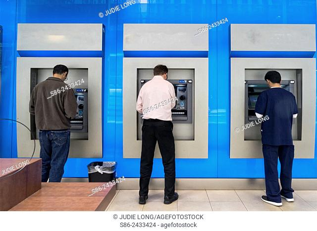 Three Men in a Bank Lobby, Using the ATM Machines