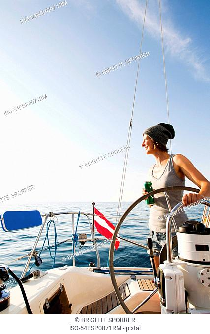Smiling woman steering on boat