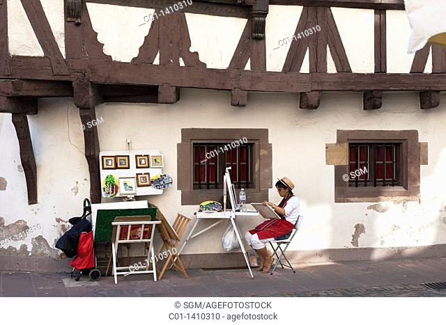 Street artist painting by half-timbered house, 'La Petite France' district, Strasbourg, Alsace, France