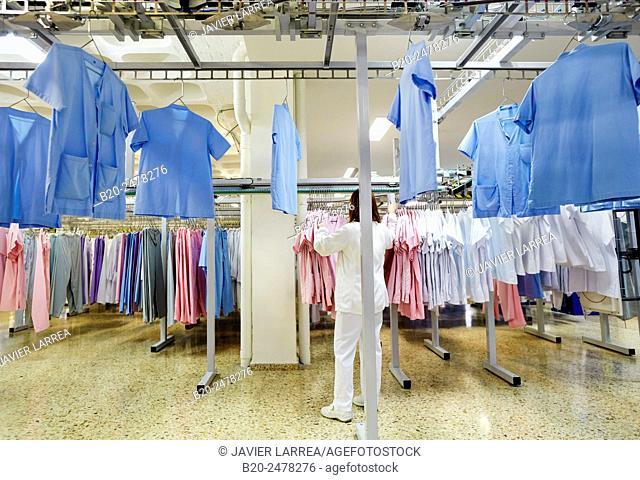 Scrubs hanging on rack in automated warehouse of hospital laundry, Hospital Donostia, San Sebastian, Basque Country, Spain