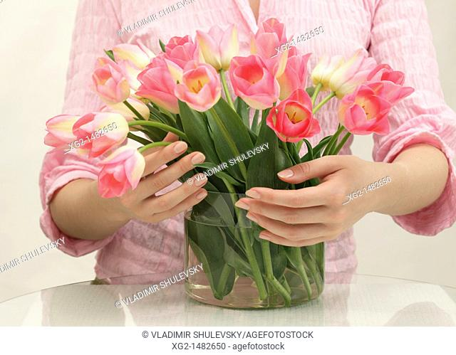 Woman putting pink tulips into a glass vase
