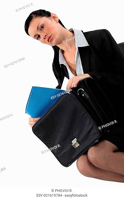 Businesswoman removing paperwork from bag