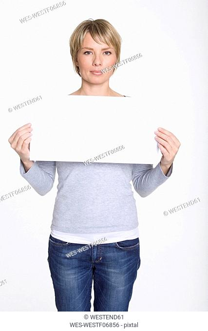 Young woman holding blank placard, portrait