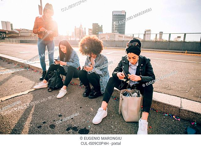 Friends sitting on kerb texting, Milan, Italy