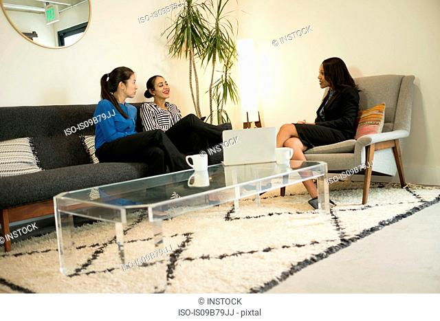 Three businesswomen sitting on office sofa, having relaxed meeting