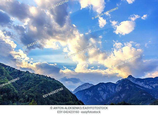 Sunlight and clouds above the hill crowned with a wood, Austria