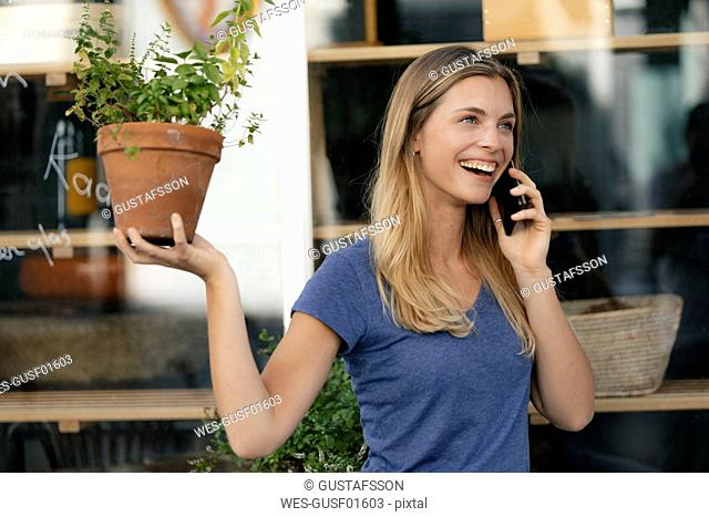Netherlands, Maastricht, laughing young woman on cell phone in the city holding flowerpot