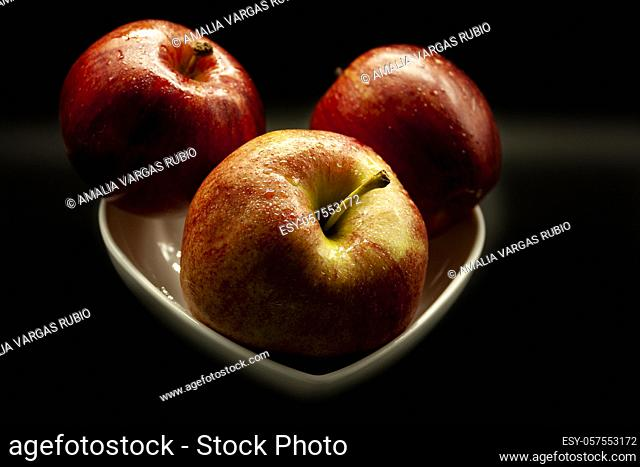 Three fresh apples arranged in a white bowl on a black background ready to eat