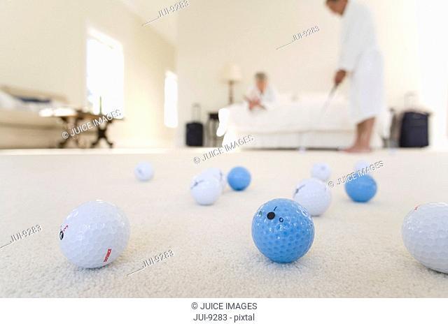 Senior couple in bedroom, man practising golf putt, focus on golf balls in foreground