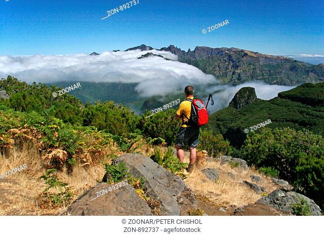 Hiker looking across to the Central Mountains of Madeira from Bica da Cana