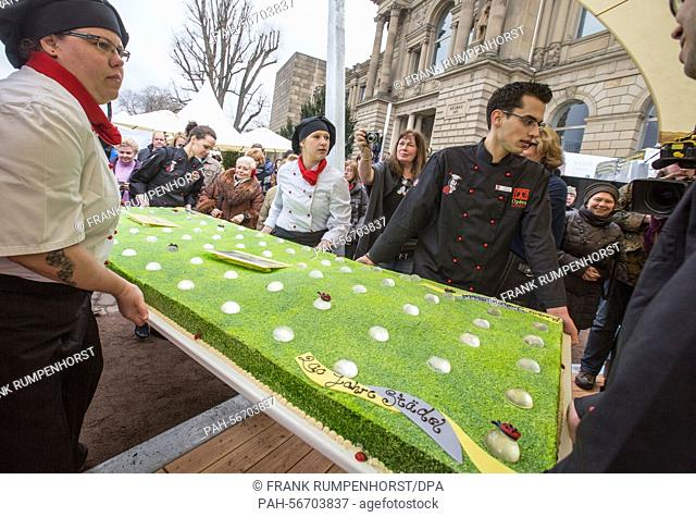 Employees of a bakery carry the birthday cake during the anniversary celebrations in Frankfurt a.M., Germany, 15 March 2015