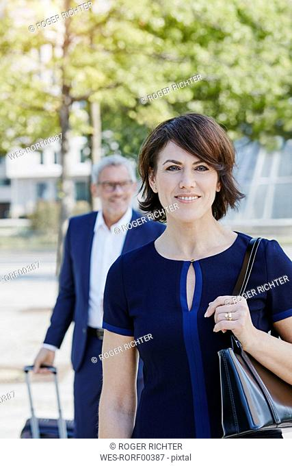 Smiling businesswoman on the go with businessman in background