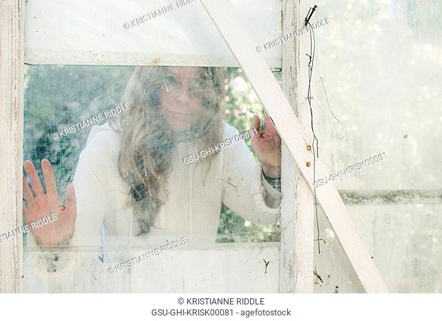 Woman Looking Through Window into Greenhouse