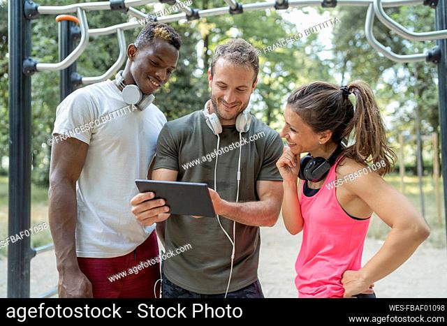 Friends having a break from exercising looking at phablet
