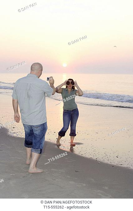 Couple in their 20's having fun on the beach of ocean city taking pictures during sunrise/sunset, she plays with donuts as glasses
