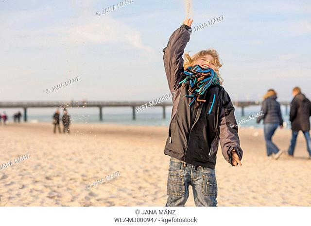 Germany, Mecklenburg-Western Pomerania, Ruegen, little boy on the beach throwing sand up in the air