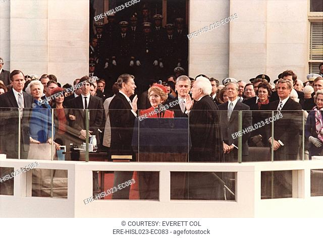 President Reagan being sworn in on Inaugural Day U.S. Capitol. Chief Justice Warren Berger leads the ceremony as Nancy Reagan holds the Bible