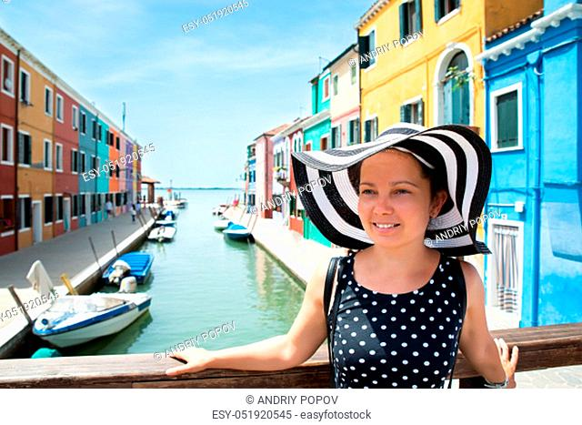 Smiling Young Woman Wearing Stripes Hat Standing In Front Of Colorful Houses At Burano Island