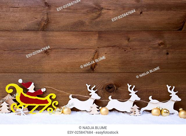 Christmas Decoration, Red Santa Claus With Yellow Sled And White Reindeer On Snow. Brown Vintage Wooden Background With Copy Space And Golden Christmas Balls