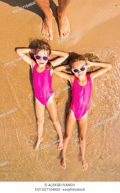 Two girls lie on his back on the surf of the sea sandy beach, there are a number of adult human foot