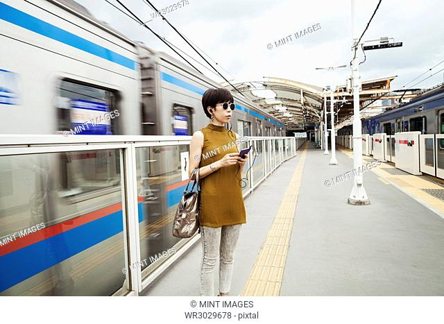 Woman wearing sunglasses standing on the platform of a subway station, Tokyo commuter