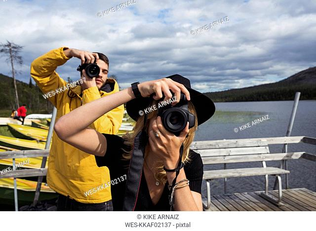 Finland, Lapland, man and woman taking pictures on jetty at a lake