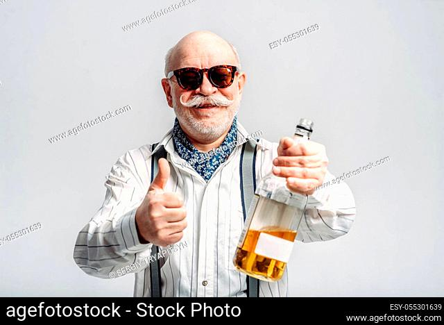 Fashionable elderly man holds the bottle of good alcohol, grey background. Mature senior looking at camera in studio, dude