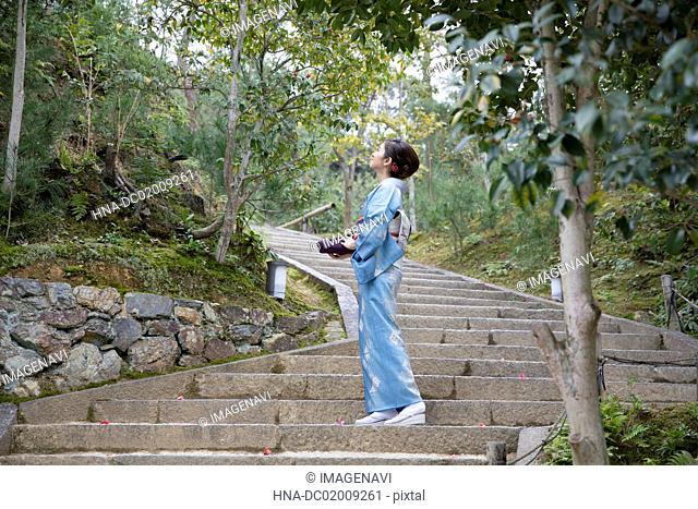 Young Japanese woman in kimono looking up on stone stairs