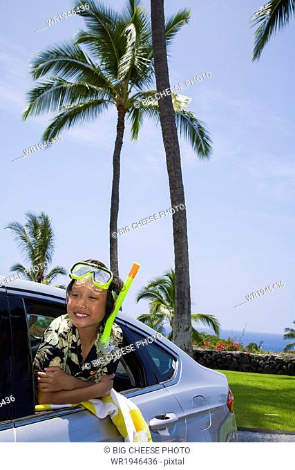 Boy wearing a scuba mask and snorkel leans out a car window