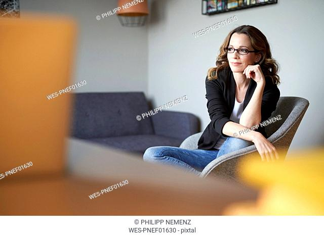 Brunette woman sitting on armchair at home looking away