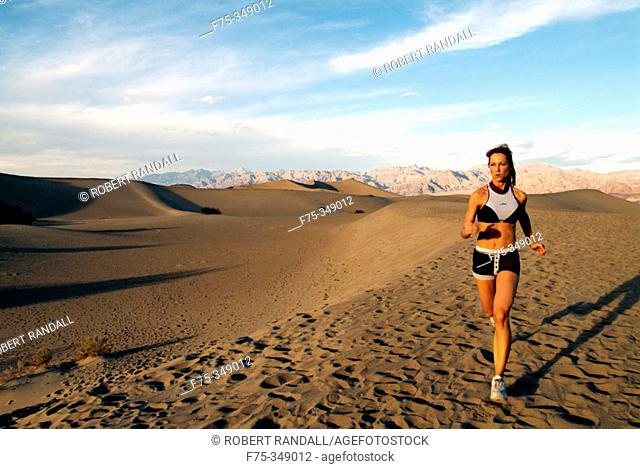 Young woman running sand dunes in Death Valley, California. USA