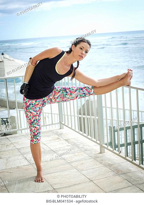 Mixed race amputee athlete stretching on balcony