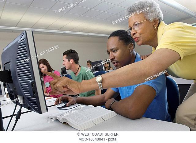 Teacher helping student in computer class