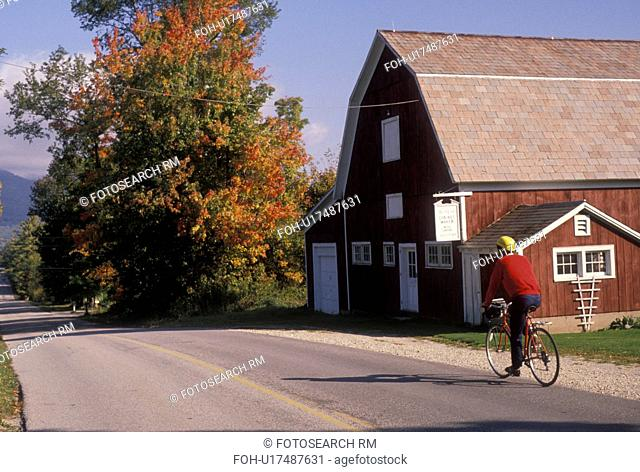 biking, barn, fall, Vermont, A man bikes along a country road past a red barn during the fall in Chiselville in Bennington County in the state of Vermont